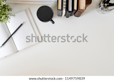 Flat lay, top view office table desk. Workspace with notebook, book, office supplies, pencil, green leaf, and coffee cup on white desk. #1149759839