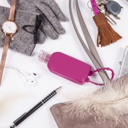 Flat lay top view photography of women  accessories with a content of bag with cleansing pocket hand sanitizer, keys, gloves, watch, earphones, and a pen