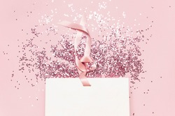 Flat lay top view White gift bag and holographic glitter confetti in the form of stars on pink background. Greeting card Festive holiday pastel backdrop. Birthday congratulations Christmas New Year