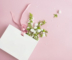 Flat lay top view White gift bag and spring flowers on a pink background. Greeting card with delicate flowers Pink floral background