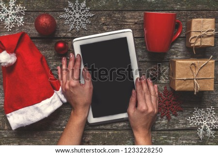 Flat lay top view. Winter Christmas composition. Woman's hands hold a tablet with a Santa hat on a wooden background with festive boxes and New Year's decor. #1233228250