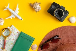 Flat lay traveler accessories on yellow background with vintage camera, airplane model, beach hat, passport, map, magnifying glass and seashells. Top view travel or vacation concept. Summer background