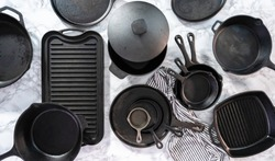 Flat lay. Variety of cast iron frying pans on a marble background.