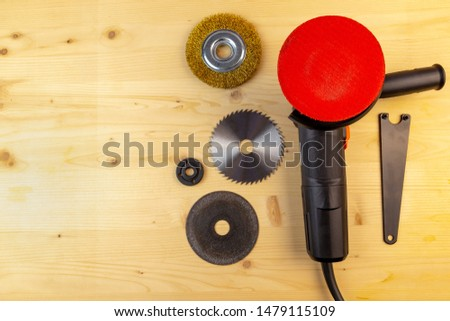 Flat lay view of a workbench with a set of tools consisting of anangle grinder with polishing disc on and a spare cutting discs for metal, wood and brushing