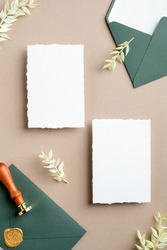 Flat lay wedding invitation cards, green envelope with seal wax stamp, dried flowers on pastel beige background. Wedding stationery set top view.