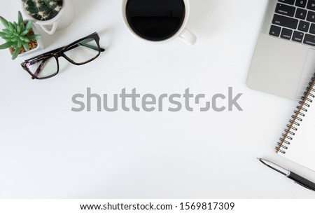 Flat lay, White office desk table with laptop, notebook, pen, black coffee cup and eyeglasses. Top view with copy space.
