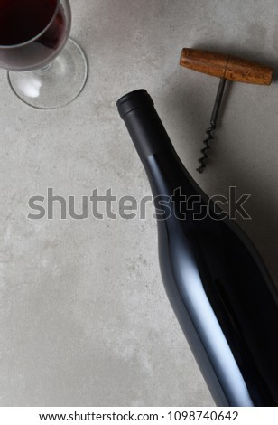 Flat lay wine bottle still life with cork screw and glass, with copy space.