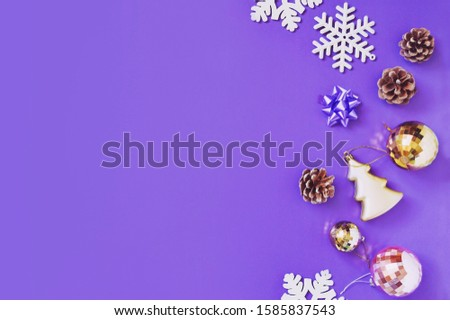Flat lay winter holiday photo. Snowflakes, pine cones, gold and pink ball and bauble. Christmas decoration on a purple background. New Year ornament. Mockup, banner, free space for text #1585837543