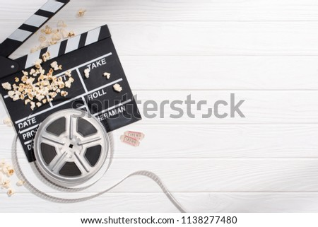flat lay with clapper board, filmstrips, popcorn and retro cinema tickets arranged on white wooden tabletop