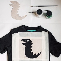 Flat lay with crafting utensils for painting a funny dinosaur silhouette on a t shirt. Fun and creative DIY activity at home for children. Idea for making a special hand made gift. School art project.
