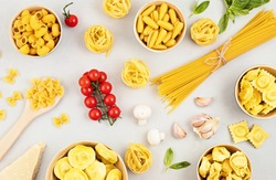 Flat lay with different types of traditional italian pasta. Penne, tagliatelle, fusilli, farfalle, spaghetti and cooking ingredients. Traditional italian cusine concept. Top view