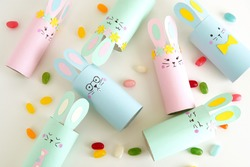 Flat lay with diy paper Easter bunnies and colorful candies, easy crafts for kids.