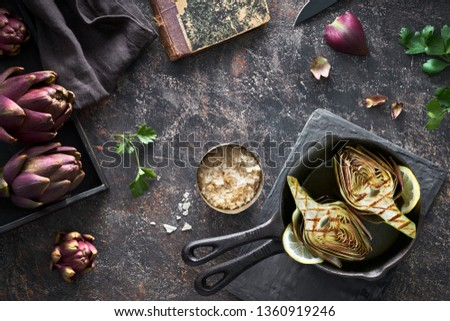 Flat lay with fresh and grilled red artishokes, whole and halved, on dark background #1360919246