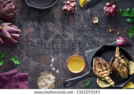 Flat lay with fresh and grilled red artishokes, whole and halved, on dark textured background with copy-space #1362293243