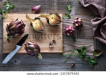 Flat lay with fresh red artishokes, whole and halved, on cutting board on rustic wooden background #1357879343