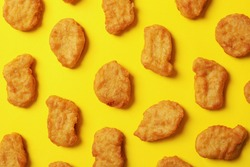Flat lay with fried chicken nuggets on yellow background