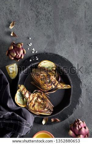 Flat lay with grilled and fresh red artishokes, whole and halved, on dark background, copy-space
