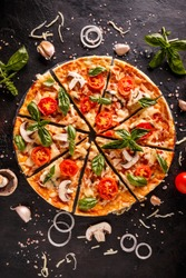 Flat lay with Italian pizza on black background and various ingredients