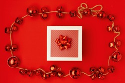 flat lay with present box and christmas jingle bells on red background.