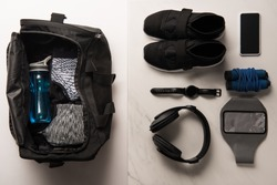 flat lay with sports bag and arranged sports equipment on white and marble