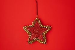 flat lay with star shaped christmas toy on red background.