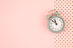 Flat lay with vintage alarm clock over the pink pastel background with golden polka dots