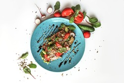 Flat lay with warm salad. Basil, radish, meat, and seeds on a blue plate. Flat lay. Restaurant menu