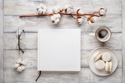 Flat lay with white photo album or book with empty cover, eyeglasses, cup of coffee, macaroons and cotton flower on white wooden aged background. Overhead view, copy space