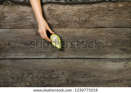 Flat lay with woman hand elegantly touching  half cut avocado on wooden background #1230775018