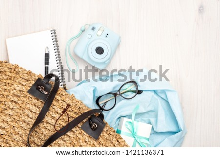 Flat lay woman bag with elegant feminine accessories on wooden desk. Top view female bag with modern photo camera, glasses, paper notepad, gift box, stuff. Summer fashion, blogger workplace concept.