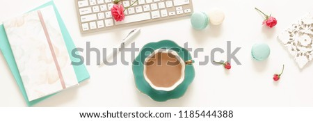 Flat lay women's office desk banner. Female workspace with laptop, flowers roses,  accessories, notebooks, glasses, cup of coffee, cosmetics on white background. Top view feminine background.