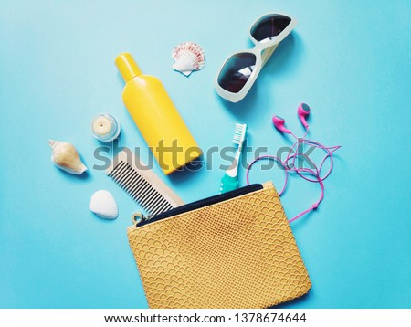 Flat lay yellow sunscreen bottle, wooden comb, toothbrush, lip balm, headphones, sunglasses and cosmetic bag. Summer kit travel accessories and beauty products