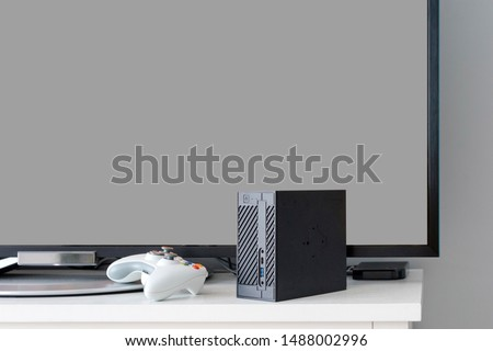 Flat LCD television on white cabinet in the living room with dark gray wall. Video gaming console and gamepad. Gamer station mockup #1488002996