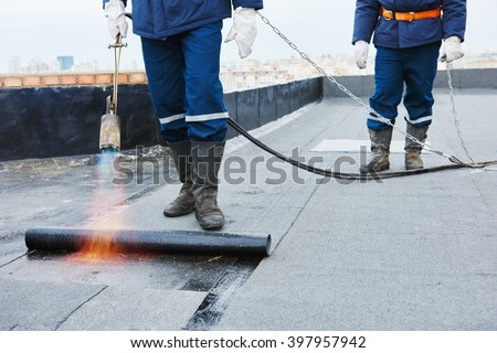 Flat roof installation. Heating and melting bitumen roofing felt