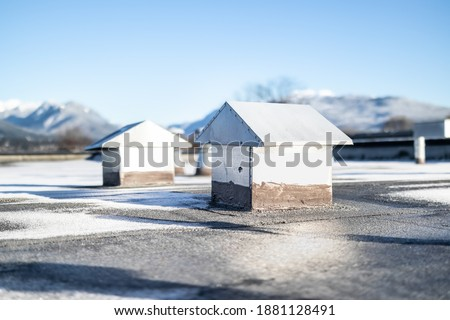 Flat roof vents on building with 2-ply SBS or modified bitumen roofing system. Group of custom made metal bathroom and laundry exhaust vents in shape of tiny houses. Selective focus. stock photo