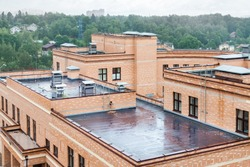 Flat roof with air conditioners top modern apartment house building mixed-use urban multi-family residential district area development.