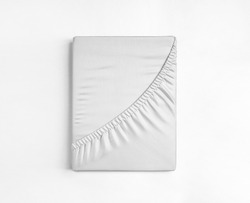 Flat sheet or bed cover folded. White fitted sheet against a white background. White sheet with elastic band.