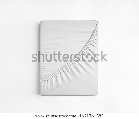 Photo of  Flat sheet or bed cover folded. White fitted sheet against a white background. White sheet with elastic band.