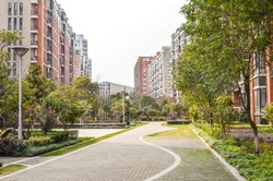Flat stone pedestrian walkway in an inner courtyard garden with green trees and grass between high-density residential apartment buildings. Ningbo, Zhejiang Province, China.