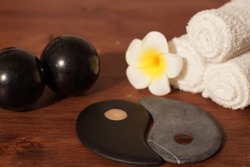 Flat stones are carved and laid out in the shape of the yin-yang sign on the table with the spa composition.