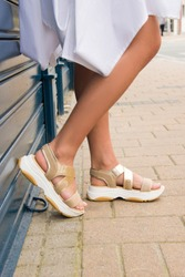 flat summer gold and white sandals with white dress close up on foot street photo