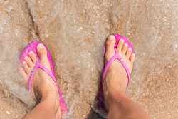 Flat top above view down of brown orange sea sand in Marineland, Florida beach with woman feet pink slippers flip-flops with wave crashing on shore