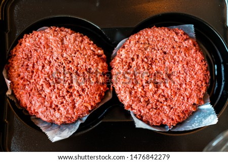 Flat top closeup of two raw uncooked red vegan plant based meat burger patties in packaging