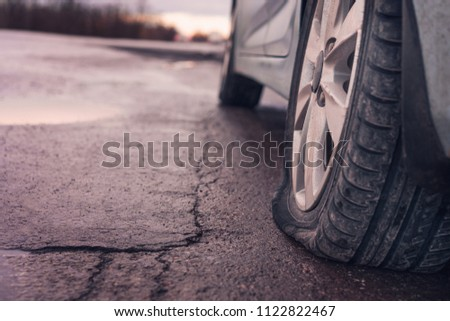 Flat tyre on road. Car tire leak because of nail pounding. Toned #1122822467