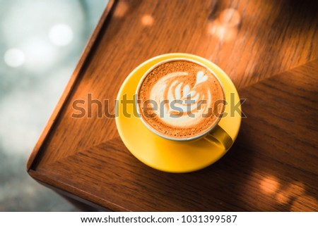 Flat white coffee in yellow cup from above on a wooden table at the hipster coffee shop. Morning sunlight effect. Latte art concept. Vintage color filter effect. Copyspace