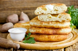 Flatbread langos langosh from potato yeast dough deep fried , Hungarian cuisine