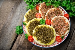 Flatbread with zaatar and meat(lahmacun) in ornament plate with parsley and tomatoes on wooden background. Arabian cuisine