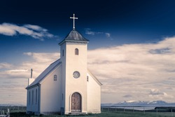 Flateyjarkirkja white lutheran church with meadow in foreground and sea  fjord with dark blue sky and mountains in the background, Flatey, Iceland
