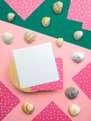Flatlay,close up top view square note sheets on round wooden base,dark green diagonal paper,ivory seashells scattered,corners of pink paper white polka dots on perimeter.Design pattern copy space.