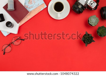 Flatlay frame arrangement with vintage film camera, lenses, glasses,  notebook, map, cup of coffee and succulents. Travel, planning or business mockup, red background, copyspace #1048074322